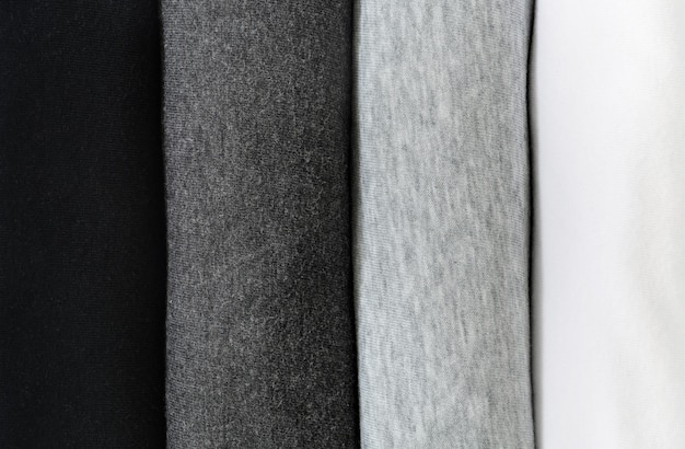 Stapel zwarte, grijze en witte t-shirts