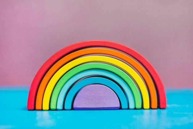 Stapelbaar regenboogstuk speelgoed op een blauwe lijst