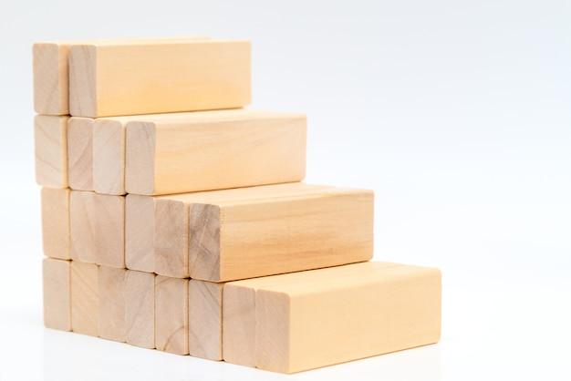 Stapelen van houten blokken in de vorm van een trap op een witte muur. ladder carrièrepad concept voor succes bedrijfsgroeiproces.