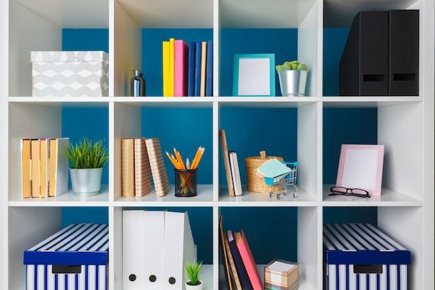 Stapels benodigdheden en papierwerk op kantoor en boekenplanken