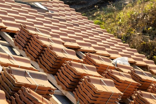 Stapels gele keramische dakpannen voor het afdekken van het dak van een woning in aanbouw