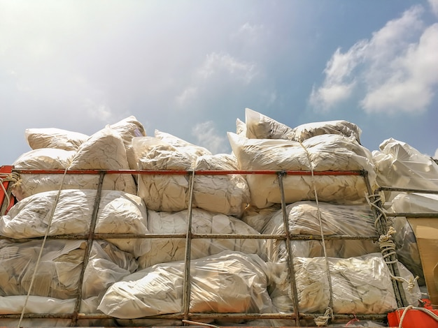 Stapels gerecycleerd papier en schuim en plastic vuilniszakken op de vrachtwagen