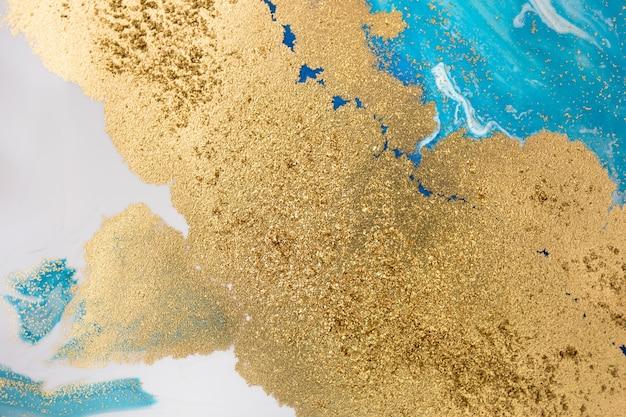 Stapels gouden pailletten op blauwe verfvlekken
