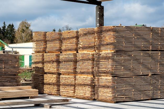 Stapels houten planken in de zagerij, planken. magazijn voor het zagen van planken op een zagerij buitenshuis. houten houtstapel van houten spatiesbouwmateriaal. industrie.