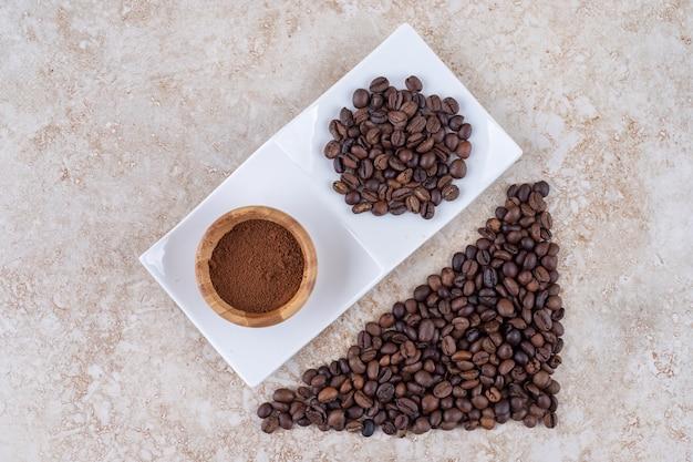Stapels koffiebonen en een kommetje gemalen koffie