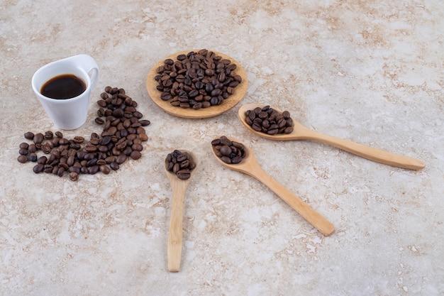 Stapels koffiebonen en een kopje koffie