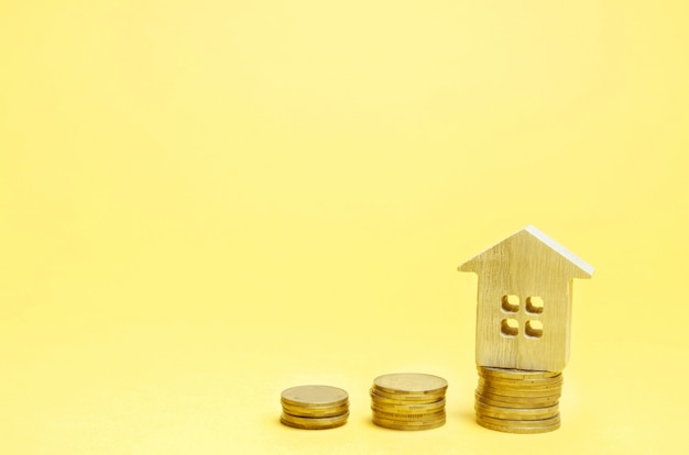 Stapels munten en een houten huis. het concept om geld te besparen voor het kopen van een huis