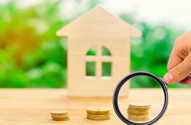 Stapels munten en een houten huis