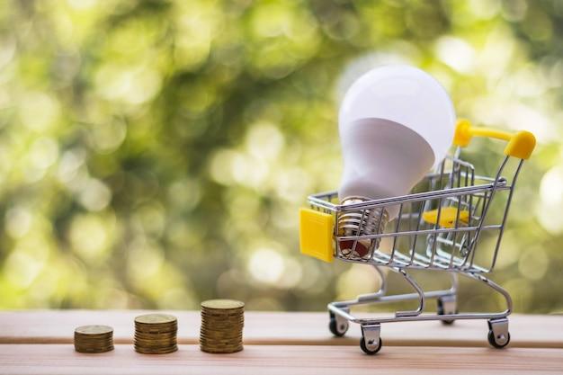 Stapels munten en energiezuinige lamp in mini winkelwagen