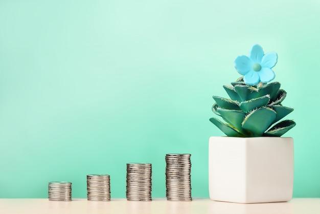 Stapels munten met bloem in pot. investeringsgroei concept.