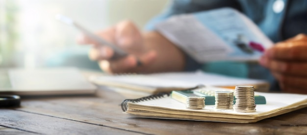 Stapels munten op een houten tafel met rekenmachine op de achtergrond controleert een man huishoudelijke rekeningen