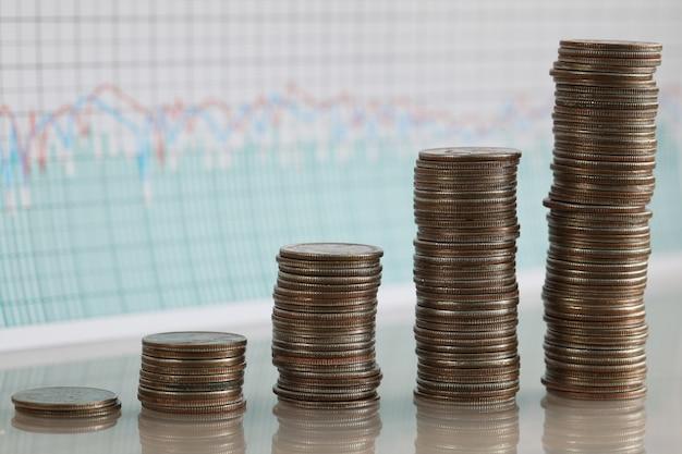 Stapels muntstukken die in rij tegen van financiële indicatorenmuur toenemen