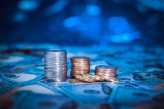 Stapels muntstukken op de achtergrond van honderd dollarsrekeningen. donkerblauw licht.