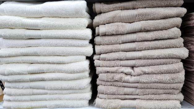 Stapels prachtige witte en grijze handdoeken in pastelkleuren worden verkocht in een vitrine in de winkel. scandinavische stijl, lagom.