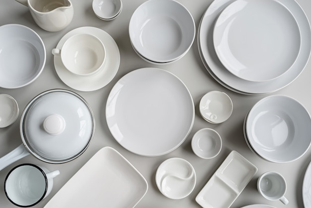 Stapels van witte keramische gerechten en tafelgerei bovenaanzicht op grijze achtergrond