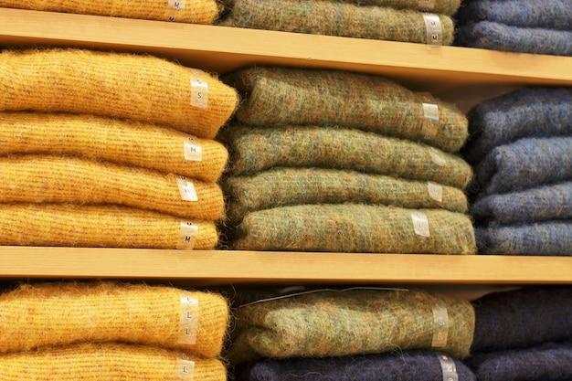 Stapels veelkleurige trui op de planken in dameskleding