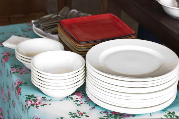 Stapels witte ronde porseleinen borden en rode vierkante borden