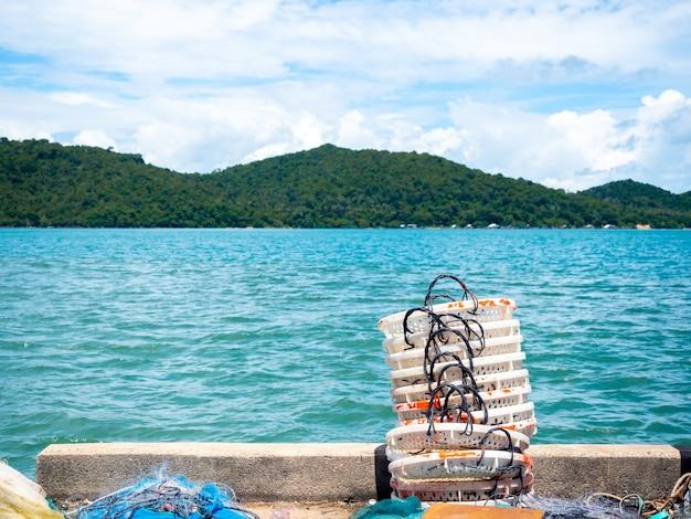 Stapelt witte manden die in de zon moeten worden gedroogd bij vissersdorp op zeegezichtachtergrond in thailand.