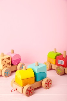 Stapeltrein peuterspeelgoed voor kleine kinderen op roze met schaduwreflectie