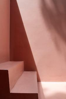 Stappen bij een roze muur met schaduwen