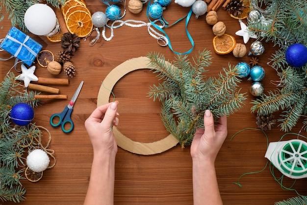 Stapsgewijs proces om thuis een kerstboomkrans te maken van vuren takken, sinaasappels en kerstballen in de zilveren en blauwe kleuren van de stier 2021.