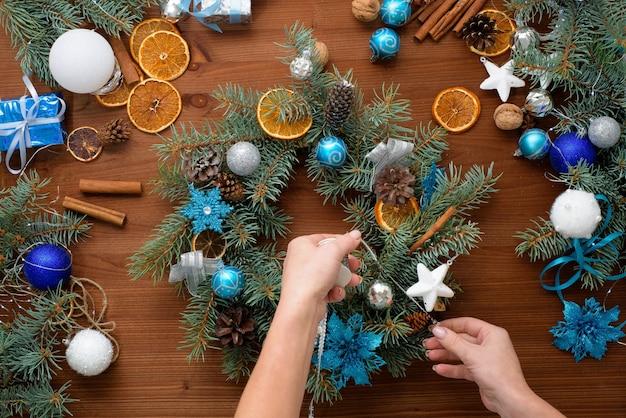 Stapsgewijs proces om thuis een kerstboomkrans te maken van vuren takken, sinaasappels en kerstballen