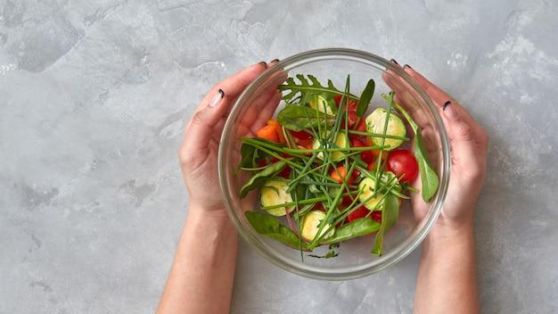 Stapsgewijs recept. verse groenten in een bord snijden, houdt het meisje een bord in handen