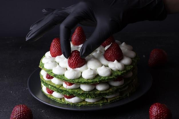 Stapsgewijze bereiding van groene cake van spinazie en aardbeien. laatste stap. handbanketbakker in zwarte handschoenen die cake versieren