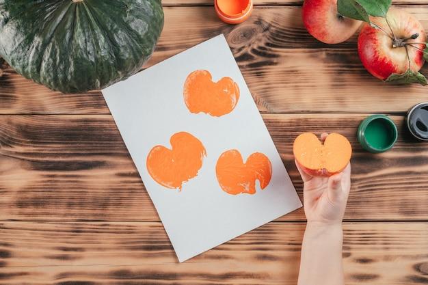 Stapsgewijze halloween-tutorial pompoen-appelprints. stap 10: de hand van het kind houdt de helft van de appel vast die in oranje gouache is geverfd