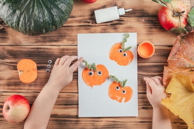 Stapsgewijze halloween-tutorial pompoen-appelprints. stap 15: hand van het kind lijmt pluizige draad als staarten aan pompoenafdrukken
