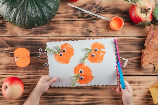 Stapsgewijze halloween-tutorial pompoen-appelprints. stap 16: kindhanden knippen afgewerkte kaart met een krulschaar