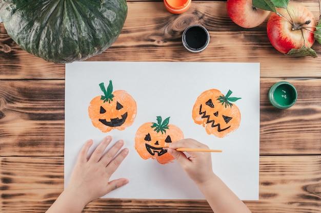 Stapsgewijze halloween-tutorial voor kinderen met pompoen-appelprints. stap 10: hand van het kind tekent ogen en mond van pompoenen met zwarte gouacheverf. bovenaanzicht