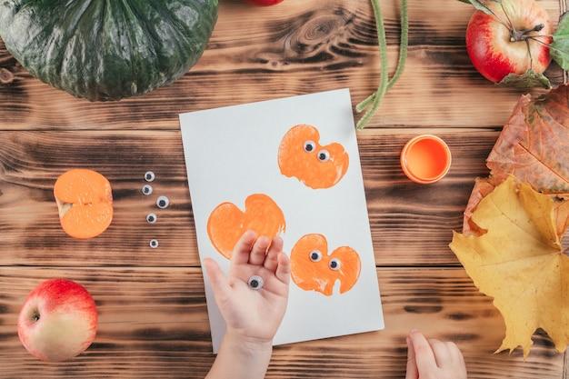 Stapsgewijze halloween-tutorial voor kinderen met pompoen-appelprints. stap 11: hand van het kind houdt ogen vast om op pompoenprint te lijmen. bovenaanzicht