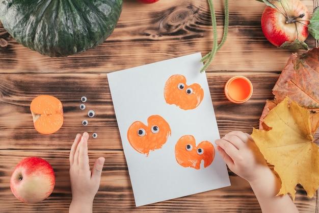 Stapsgewijze halloween-tutorial voor kinderen met pompoen-appelprints. stap 12: de kinderhand plakt de ogen op alle pompoenafdrukken. bovenaanzicht