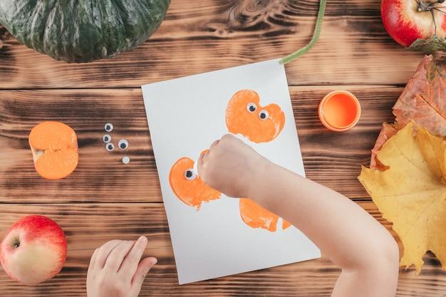 Stapsgewijze halloween-tutorial voor kinderen met pompoen-appelprints. stap 13: de kinderhand druppelt een druppel lijm op de pompoenprint. bovenaanzicht