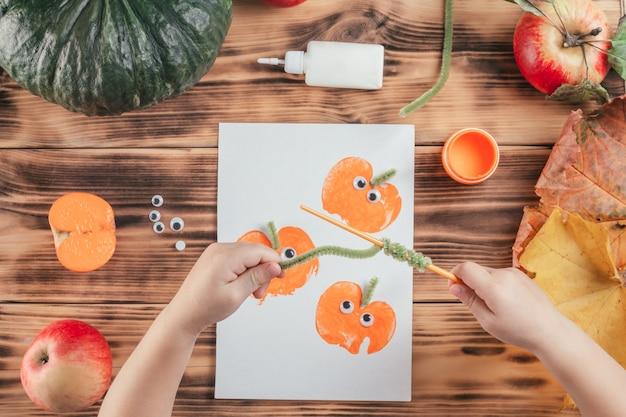 Stapsgewijze halloween-tutorial voor kinderen met pompoen-appelprints. stap 14: kind hand wind groene pluizige draad rond potlood