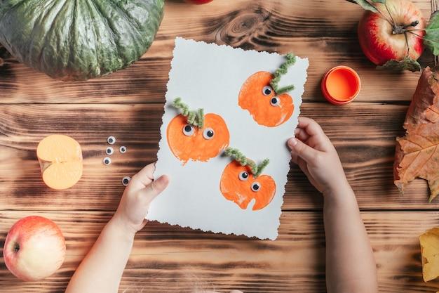 Stapsgewijze halloween-tutorial voor kinderen met pompoen-appelprints. stap 17: handen van het kind houden de voltooide kaart vast, bovenaanzicht