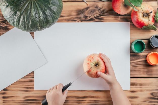 Stapsgewijze halloween-tutorial voor kinderen met pompoen-appelprints. stap 2: snijd appel doormidden met mes, bovenaanzicht