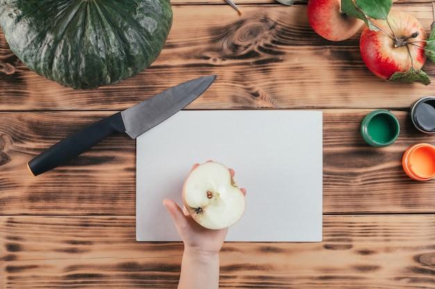 Stapsgewijze halloween-tutorial voor kinderen met pompoen-appelprints. stap 3: hand van het kind houdt de ene helft van de appel vast, bovenaanzicht