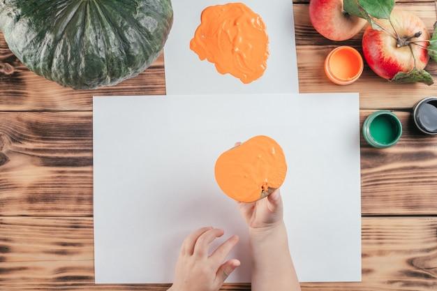 Stapsgewijze halloween-tutorial voor kinderen met pompoen-appelprints. stap 7: de hand van het kind houdt de helft van de appel vast die in oranje gouache is geverfd om een afdruk te maken. bovenaanzicht