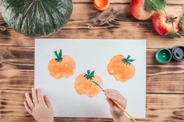 Stapsgewijze halloween-tutorial voor kinderen met pompoen-appelprints. stap 9: hand van het kind tekent staarten naar pompoenen met groene gouacheverf. bovenaanzicht