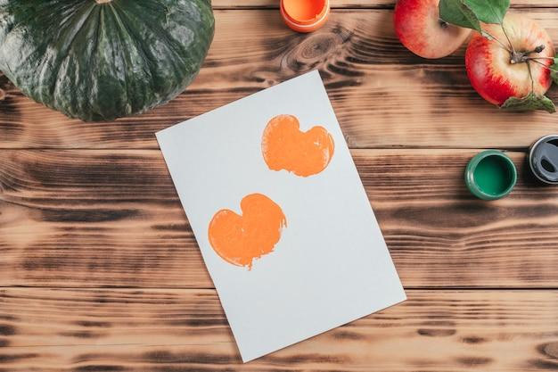 Stapsgewijze halloween-tutorial voor kinderen met pompoen-appelprints. stap 9: prints op papier van een halve appel geschilderd in oranje gouacheverf. bovenaanzicht