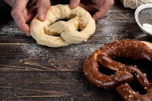 Stapsgewijze instructies voor het maken van pretzels. de kok rolt het deeg uit en rolt de krakeling uit