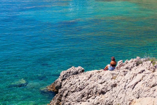 Stara baska, kroatië. meisje leest een boek zittend op de rots naast de zee