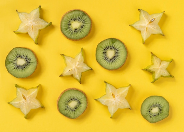 Starfuit en kiwiplakken over gele achtergrond.