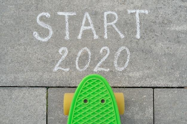 Start 2020 geschreven in krijt op grijze stoep, skateboard vóór de tekst.