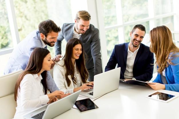 Start commercieel team bij het samenkomen in modern helder bureaubinnenland en werkend aan laptop