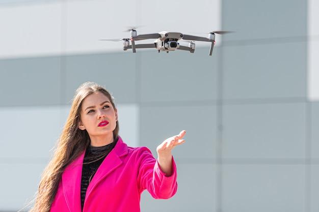 Start de drone en lanceer uit handen. intreepupil jonge vrouw op de achtergrond, focus op de quadcopter