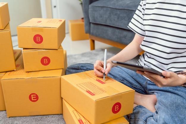 Start klein bedrijfsconcept, jonge vrouweneigenaar die en aan de doos aan klant bij de bank in huisbureau werken verpakken, bereidt de verkoper de levering voor.