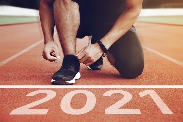 Start met nieuwjaarsplannen start van man loopt op het rennen van het veld met zonsonderganglicht doel van het succes concept